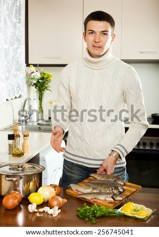 Man is thinking how to cook fish in fryingpan at kitchen - stock photo