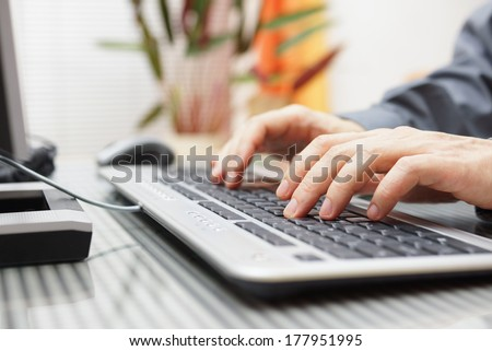 man  is typing on keyboard at home - stock photo