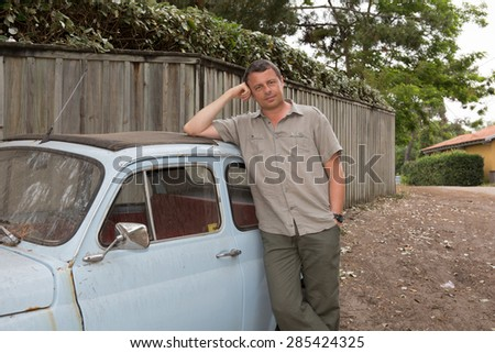 Man is waiting for someone in front of a small  vintage car