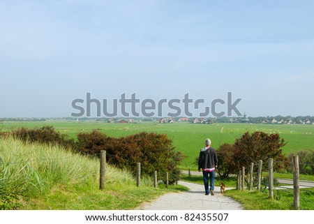 Man is walking at the Dutch island Ameland - stock photo