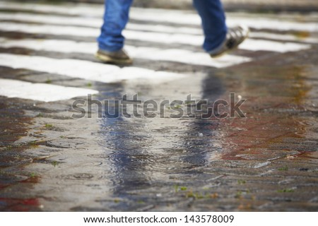 Man is walking on the zebra crossing in rain - selective focus - stock photo