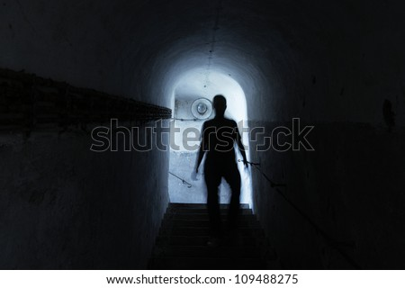 Man is walking through dark underground - blurred motion - stock photo