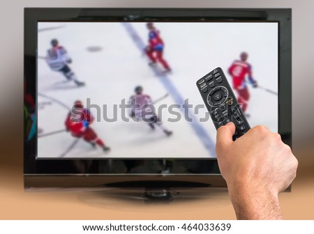 Man is watching hockey match on TV and holds remote controller in hand