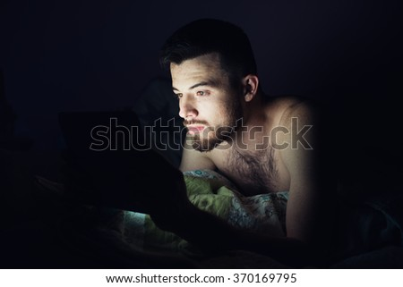 Man  is working at night, lying on the sofa in the living room with tablet. student looks tablet pc late at night before sleep in the room