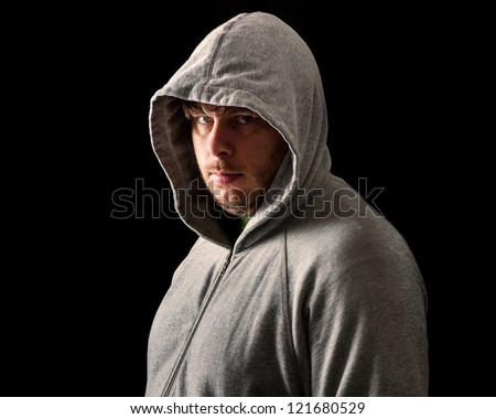 Man Isolated against a black background wearing a hoodie style sweater.