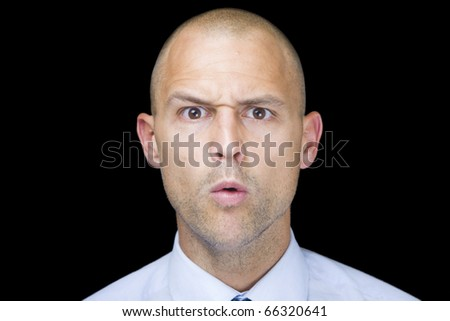 Man isolated over a black background with a humorous, confused look on his face.