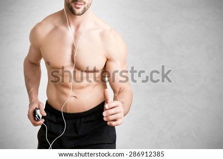 Man jogging and listening to music on his mp3 player - stock photo