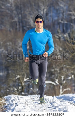 man jogging in the snow - stock photo