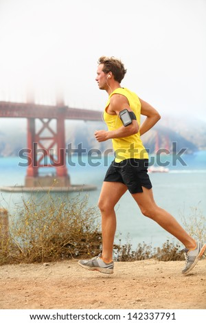 Man jogging - male running in San Francisco. Sporty fit young man jogger along a dirt track alongside San Francisco Bay and Golden Gate Bridge. Runner listening to training music from smartphone. - stock photo