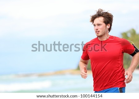 Man jogging on beach. Male runner running listening to music on mp3 player or smart phone. Young caucasian male fitness sport model in red t-shirt.