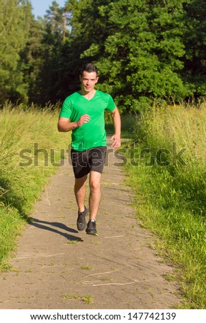 Man jogging on road outdoors  - stock photo