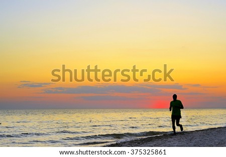 Man jogging on the beach at a beautiful sunset.