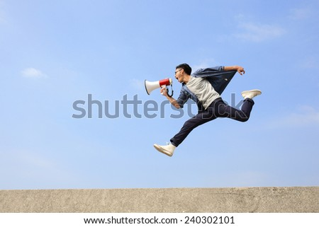 man jump and shout by megaphone with blue sky background, asian - stock photo
