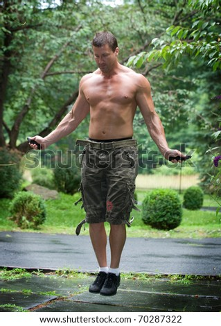 Man jump roping with shirt off in the outdoors.  Ripped muscles and six pack abs. Jumping at a high speed. - stock photo