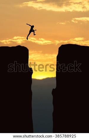 Man jump through the gap between hill ,Business concept  - stock photo