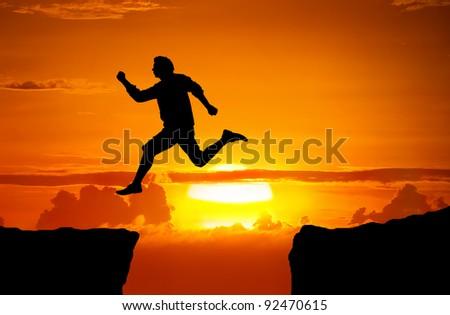 Man jump through the gap between the cliff - stock photo