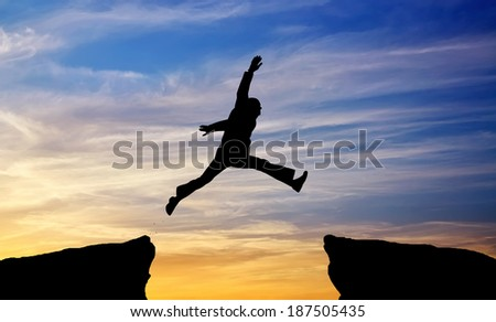 Man jump through the gap on sunset fiery background. Element of design.