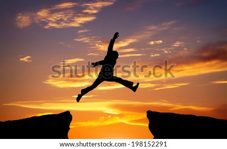 Man jump through the gap on sunset fiery background. Element of design.  - stock photo