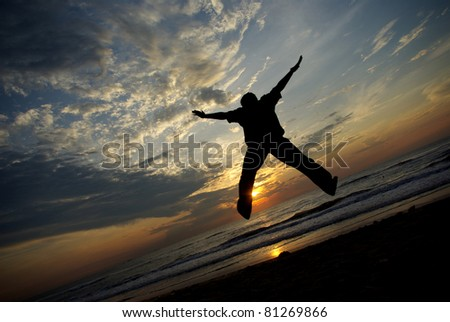 Man jump with full of enjoy taken with sunset background. - stock photo