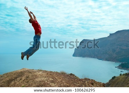 Man jumping cliff against sea and mountain with blue sky