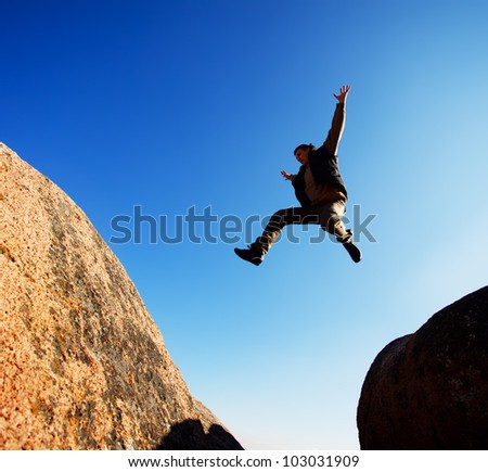 man jumping cliff with blue sky - stock photo