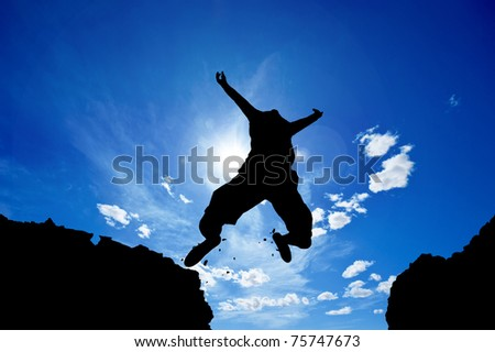 man jumping from a cliff over vivid blue sky - stock photo