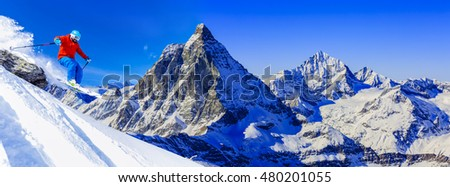 Man jumping  from the rock, skiing on fresh powder snow with Matterhorn in background in Swiss Alps.