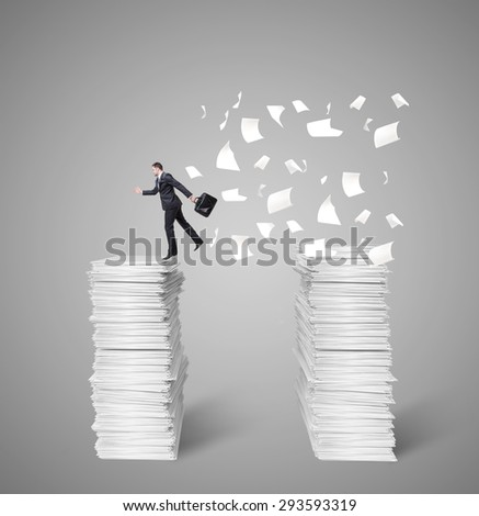 man jumping from top to top of a mountain of papers - stock photo