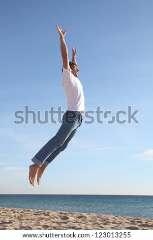 Man jumping happy in the beach with a blue sky in the background - stock photo