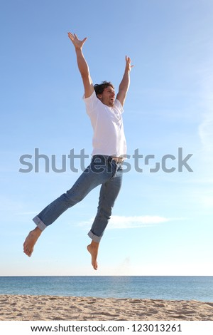 Man jumping happy in the beach with a blue sky in the background