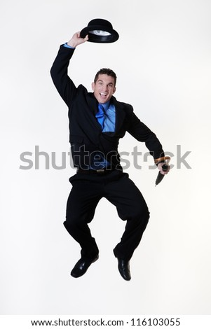 man jumping in the air holding a bowler hat and umbrella