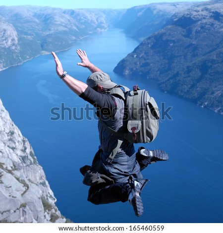 Man jumping off a cliff - stock photo