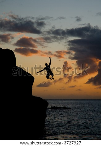 Man jumping off a rock in Waimea Beach - stock photo