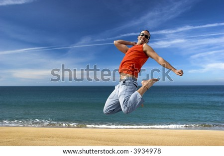 Man jumping on a the beach with a beautiful cloudy sky - stock photo
