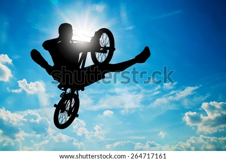 Man jumping on bmx bike performing a trick against sunny sky. Extreme sport - stock photo