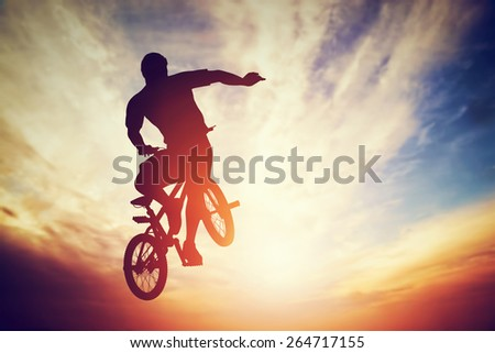 Man jumping on bmx bike performing a trick against sunset sky. Extreme sport - stock photo