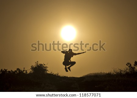 Man jumping on the background of the stunning sunset - stock photo