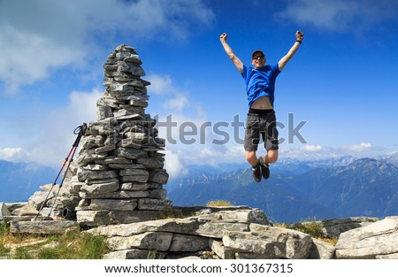 Man jumping out of joy beside a large cairn on a mountaintop. - stock photo