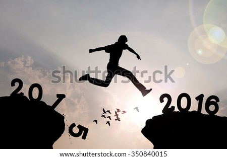 Man jumping over precipice on sunlight background , new year concept