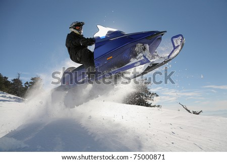 man jumping snowmobile through powder - stock photo