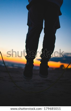 man jumping the rope on sunset - stock photo