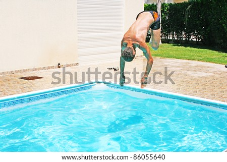 Man jumping to swimming pool.