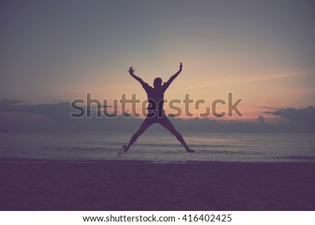 man jumping with hands up on the beach