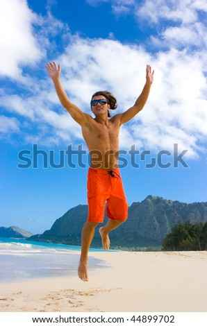 Man jumping with joy on the sand beach