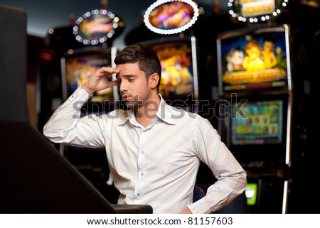 man just loosing at the slot machine, being sad - stock photo
