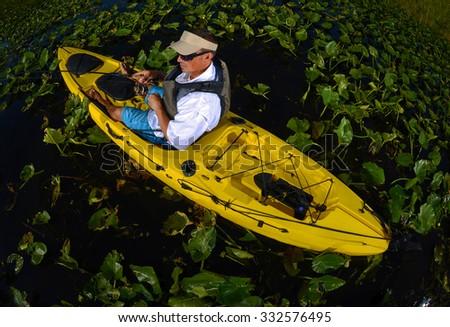 man kayak fishing in lily pads in yellow kayak - stock photo