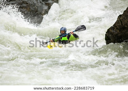 Man kayaking down class IV Boulder Drop rapid on the Skykomish River in Washington State.  - stock photo