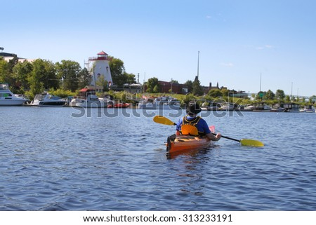 Man kayaking on the Saint John River near downtown  Fredericton, New Brunswick with it's marina and lighthouse on waterfront - stock photo