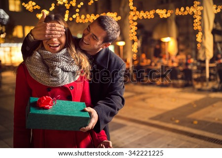 Man  keeps his girlfriend eyes covered while  she giving a gift , romantic surprise for Christmas - stock photo