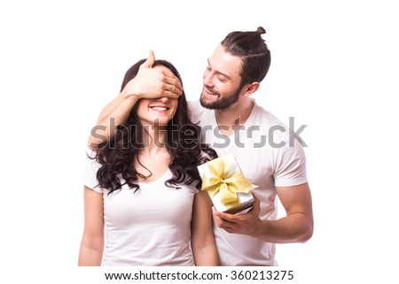 Man keeps his girlfriend eyes covered while she giving a gift , romantic surprise for Valentine Day. Man near woman. Caucasian couple.White background. - stock photo